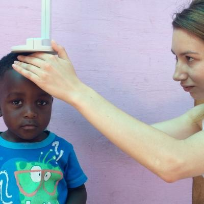 Female intern measuring a child and gaining valuable work experience with Projects Abroad giving nutriton advice whilst on a nutritional internship in South Africa.